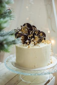Weihnachts hausgemachter weißer kuchen auf glasständer mit tannenbaum, weihnachtsdekoration