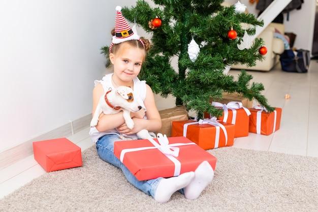 Weihnachts-, haustier- und feiertagskonzept - kind in der weihnachtsmütze mit einem jack russell terrier welpen