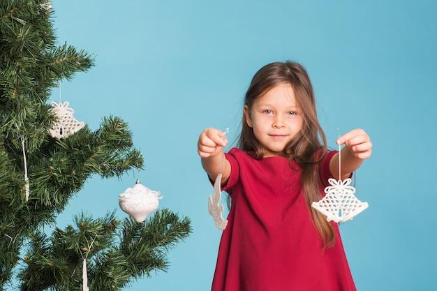 Weihnachts-, kindheits- und personenkonzept - kleines mädchen, das den weihnachtsbaum verziert
