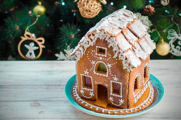 Weihnachts-lebkuchenhaus mit glasur auf holztisch