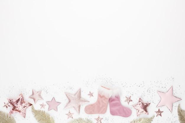 Weihnachts minimalistische und einfache komposition in rosa farbe. weihnachtsstern, dekorationen auf weißem hintergrund. flache lage, draufsicht mit kopierraum