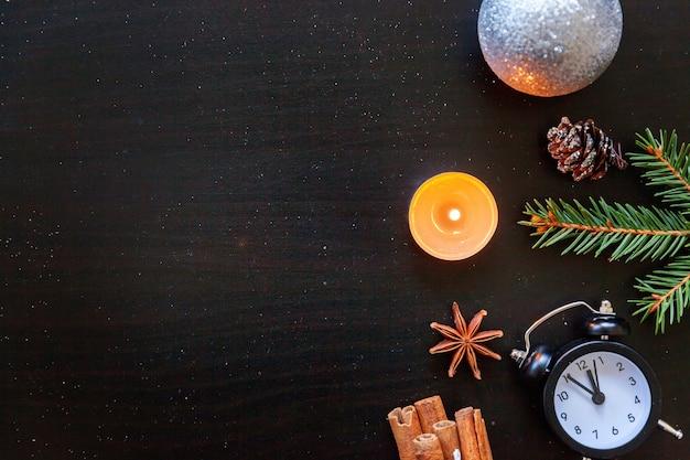 Weihnachts-neujahr-kompositionsrahmen aus winterobjekten tannenzweig-ornamentkerzenuhr auf dunklem schwarzem hintergrund