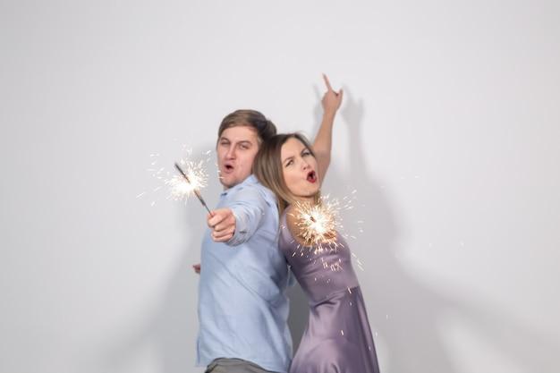 Weihnachts-, neujahrs-, party- und feierkonzept - junges paar mit wunderkerzen, das zurückbleibt