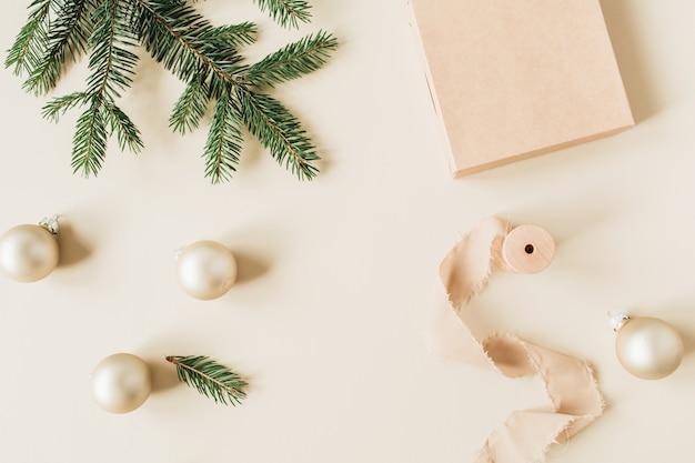 Weihnachts-neujahrsfeiertagszusammensetzung mit tannennadelzweigen, geschenkbox, bändern und goldenen weihnachtskugeln auf beige