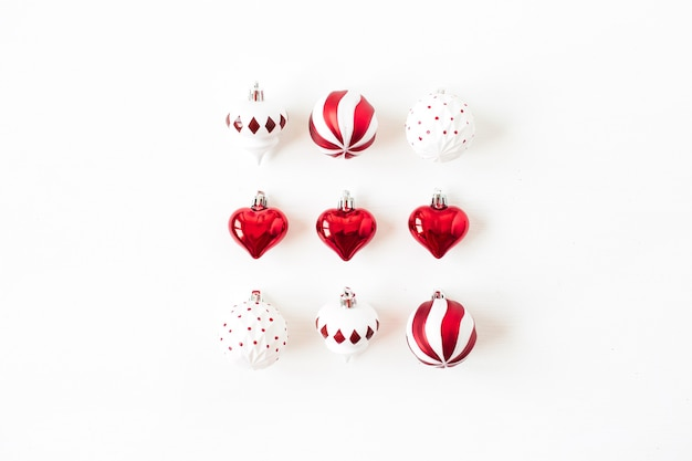 Weihnachts-neujahrsfeiertagszusammensetzung. rote und weiße weihnachtskugeln kugeln auf weiß