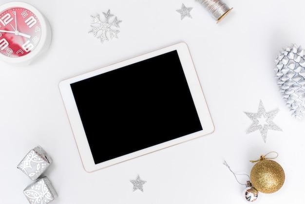 Weihnachts- oder des neuen jahreshintergrund ipad tablet-goldglaskugeln, kegel auf einem weißen gipshintergrund