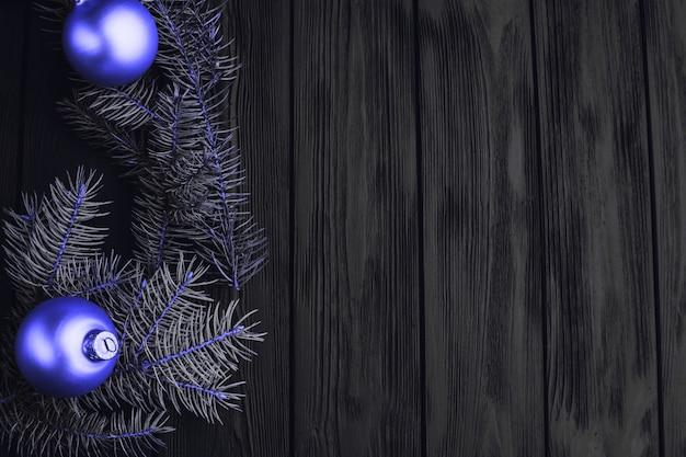 Weihnachts- oder des neuen jahrespielzeugdekorationen goldene bälle und pelzbaumast rustikal auf hölzernem hintergrund
