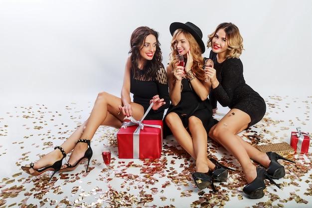 Weihnachts- oder geburtstagsfeier. drei schöne frauen sitzen auf dem boden und trinken cocktails. beste freunde packen geschenke aus. golden funkelndes konfetti. weißer hintergrund. wellenförmige frisur.