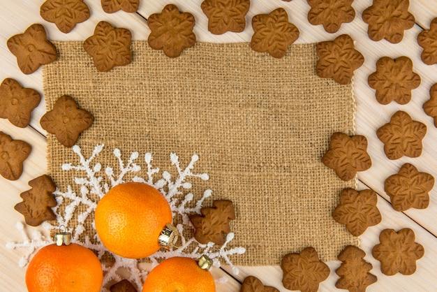 Weihnachts- oder neujahrs-mandarinen und lebkuchenplätzchen mit schneeflocken gerahmt auf hölzernem hintergrund mit braunem sackhintergrund