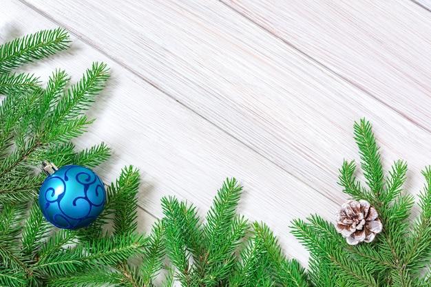 Weihnachts- oder neujahrsdekorationen hintergrundtannenzweige und blaues weihnachtsspielzeug