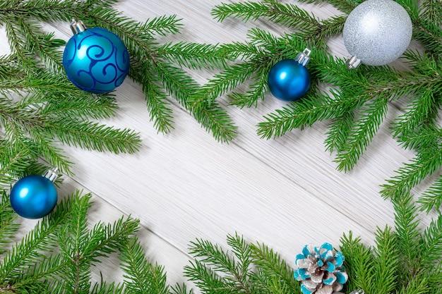 Weihnachts- oder neujahrsdekorationshintergrund - tannenzweige und blaues weihnachtsspielzeug