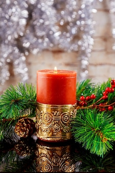 Weihnachts- oder neujahrsdunkle komposition mit brennenden roten kerzen, tannenzweigen, tannenzapfen, schneeflocken und beeren auf altem holzhintergrund, getöntes bild, selektiver fokus