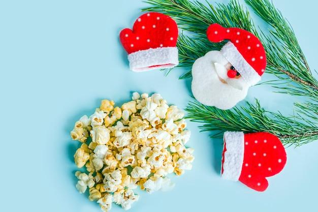 Weihnachts- oder neujahrsfilmkonzept. tannenzweig, weihnachtsmannspielzeug und popcorn