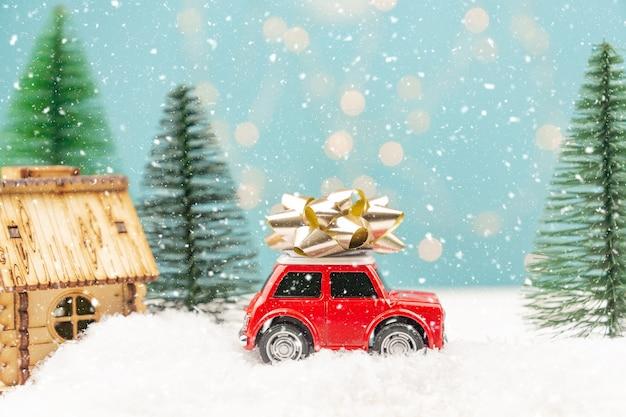 Weihnachts- oder neujahrsgrußkarte mit rotem spielzeugauto und weihnachtsbaumminiatur und weihnachtslichtern