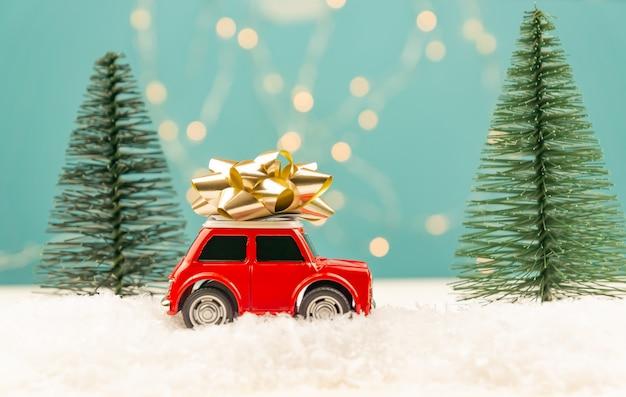 Weihnachts- oder neujahrsgrußkarte mit rotem spielzeugauto und weihnachtsbaumminiatur