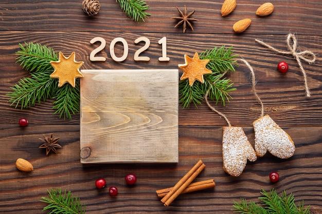 Weihnachts- oder neujahrshintergrund mit hölzernem modell und fichtenzweigen auf braunem tisch