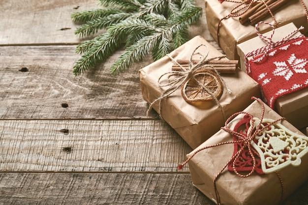 Weihnachts- oder neujahrshintergrund mit tannenzweigen, weihnachtskugeln, geschenkbox, holzschneeflocken und sternen auf dunklem holzhintergrund. platz für deinen text