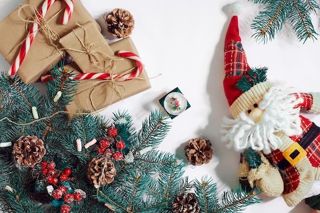 Weihnachts- oder neujahrshintergrund: pelzbaum, äste, geschenke, dekoration auf weißem hintergrund. platz für ihren text, wünsche, logo. attrappe, lehrmodell, simulation. ansicht von oben. platz kopieren. stillleben. flach legen