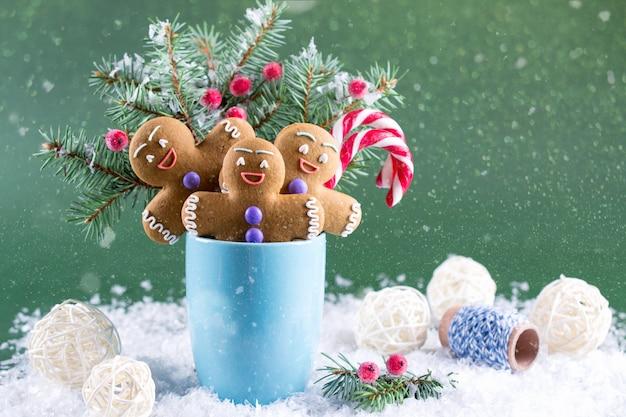 Weihnachts- oder neujahrskarte. tasse mit tannen, zuckerstangen und ingwer-männer-keksen.
