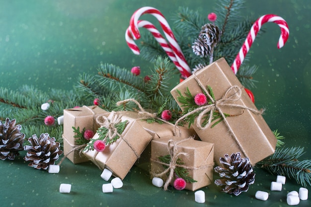 Weihnachts- oder neujahrskarte. tasse mit tannen, zuckerstangen. verpacken von geschenken in vintage beige bastelpapier und natürlichem dekor.