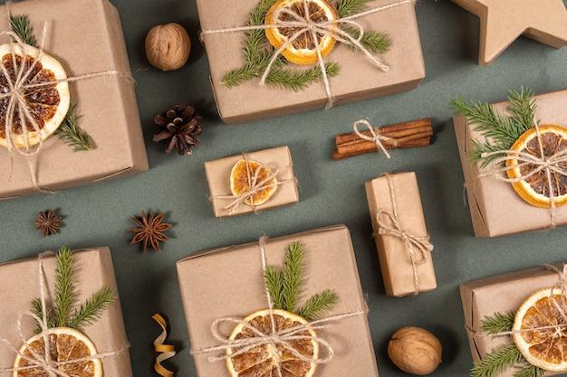 Weihnachts- oder neujahrskomposition. schachteln verziert mit bastelpapier, getrockneten orangen, fichtenzweigen und naturdekor. konzept zero waste, umweltfreundliche frohe weihnachten. draufsicht flache lage