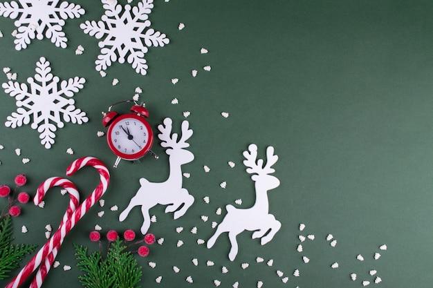 Weihnachts- oder neujahrswohnung lag mit holzfigur von hirschen und schneeflocken, tannen, zuckerstangen und roter uhr. auf grünem hintergrund.