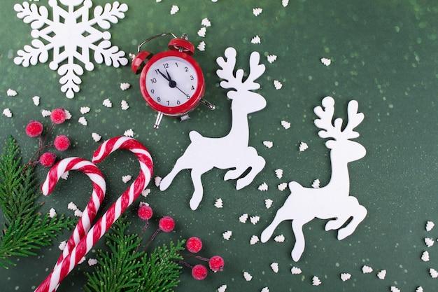 Weihnachts- oder neujahrswohnung lag mit holzfigur von hirschen und schneeflocken, tannen, zuckerstangen und roter uhr.