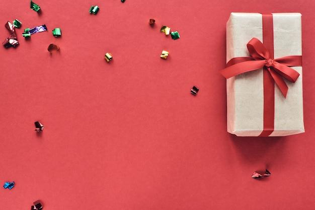Weihnachts- oder valentinstagkomposition mit kopierraum. geschenkbox mit rotem band und konfetti-dekorationen auf buntem hintergrund des pastellpapiers.