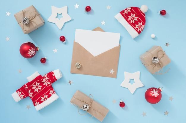 Weihnachts- oder winterzusammensetzung mit umschlag und roten dekorationen auf blauem pastellhintergrund. neues jahr-konzept.