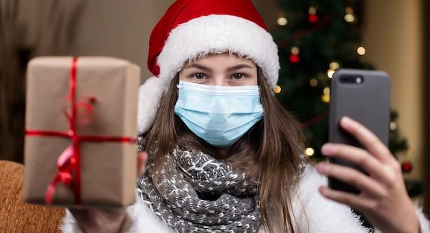 Weihnachts-online-grüße. ein junges mädchen in einem weihnachtsmannhut und einer medizinischen maske spricht unter verwendung eines smartphones für videoanruffreunde und -eltern. weihnachten während des coronavirus
