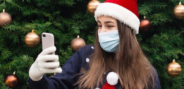 Weihnachts-online-grüße. schließen sie herauf porträt der frau, die einen weihnachtsmannhut und eine medizinische maske mit emotion trägt. vor dem hintergrund eines weihnachtsbaumes. coronavirus pandemie