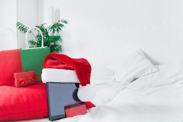 Weihnachts-online-shopping von zu hause oder lieferung lebensmittelkonzept mit zusammensetzung des mobilen tablets mit weihnachtsmütze, bankkreditkarte, papiertüten. neujahrsverkäufe. speicherplatz kopieren