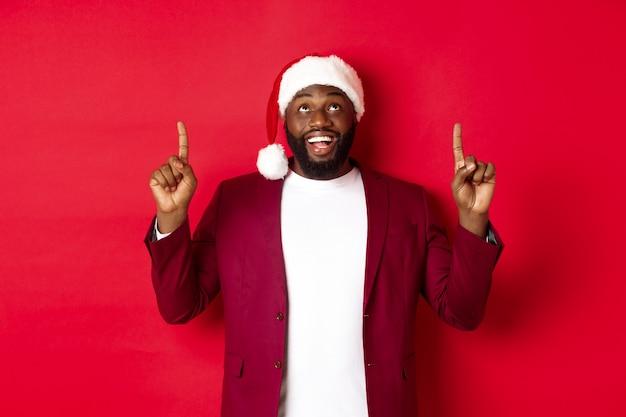 Weihnachts-, party- und feiertagskonzept. fröhlicher schwarzer mann, der neujahrs-promo betrachtet, mit den fingern nach oben zeigt und lächelt und auf rotem hintergrund steht.