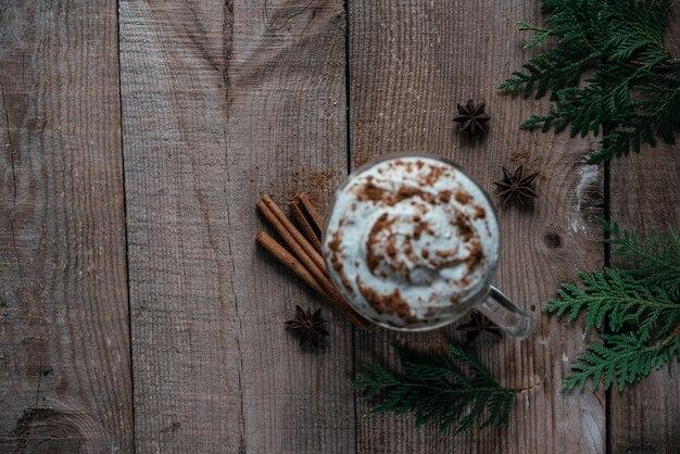 Weihnachts-schlagsahne heiße coca mit zimt, anis-sternen und thuja-zweigen auf holzhintergrund-draufsicht, weihnachts- und neujahrsgetränken