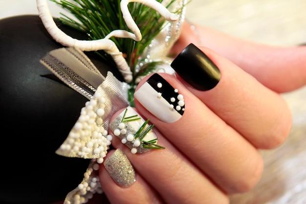 Weihnachts-schwarzweiss-maniküre mit silbernen kugeln und weihnachtsverzierung auf weiblicher hand schließen oben.