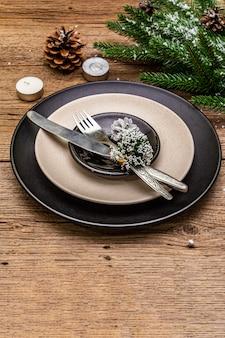 Weihnachts- und abendessengedeck des neuen jahres. immergrüner tannenbaumast, kerzen, kegel, keramikplatten, gabel und messer.
