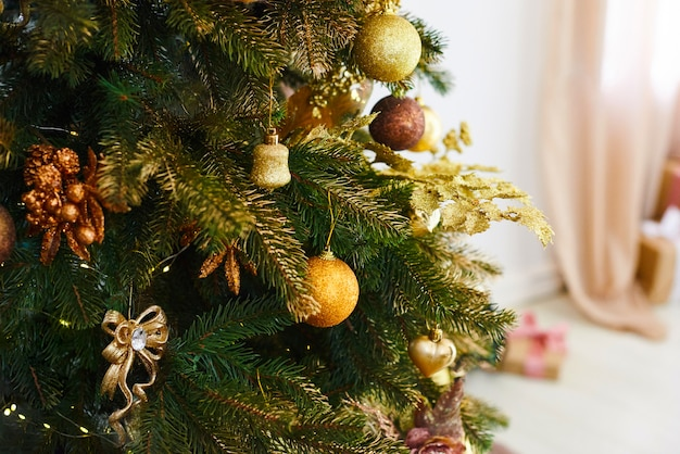 Weihnachts- und des neuen jahresbaum verziert mit goldenen spielwaren. urlaub eingerichtetes zimmer