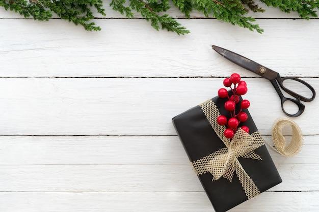 Weihnachts- und des neuen jahreshintergrund mit handwerks- und handgemachter geschenkbox auf weißem hölzernem hintergrund. kreatives flaches layout und draufsichtzusammensetzung