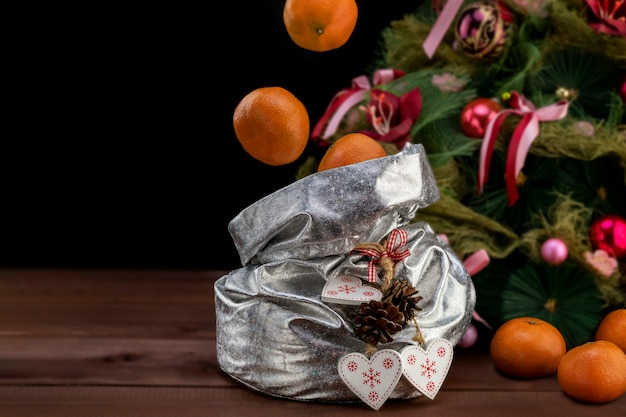 Weihnachts- und des neuen jahreskonzept mit den tangerinen, die in eine tasche mit geschenken auf holztisch fliegen