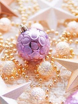 Weihnachts- und des neuen jahressterndekorationen auf weiß gestrickt. metallglühbirnen mit zartem muster, goldenen perlen und violetten kugeln.
