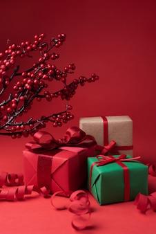 Weihnachts- und feiertagsgeschenke in bunten verpackungen und serpentinen auf rotem grund
