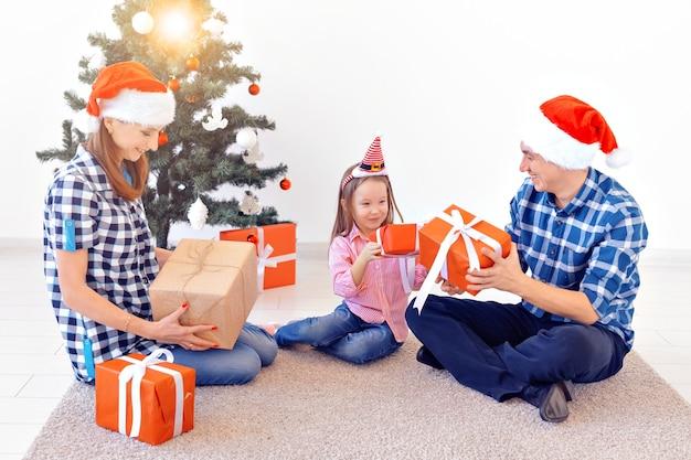 Weihnachts- und feiertagskonzept - familieneröffnungsweihnachtsgeschenk vor baum.