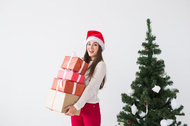 Weihnachts- und feiertagskonzept - frau in der weihnachtsmütze mit vielen geschenken