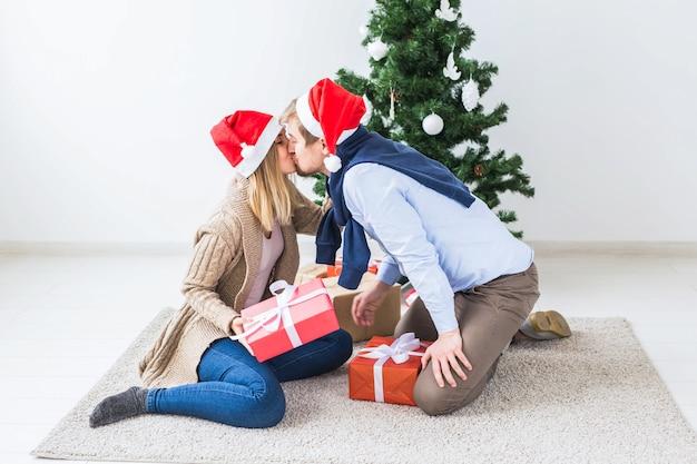 Weihnachts- und feiertagskonzept - junges glückliches paar, das weihnachtsmützen trägt, die geschenke zu hause öffnen.