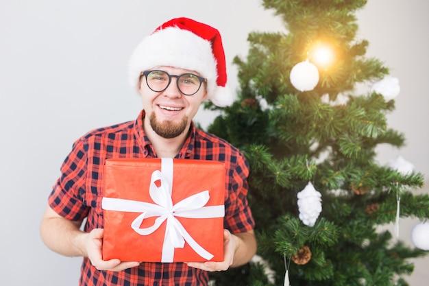 Weihnachts- und feiertagskonzept - lustiger mann in weihnachtsmütze, der ein geschenk zu hause im wohnzimmer hält.