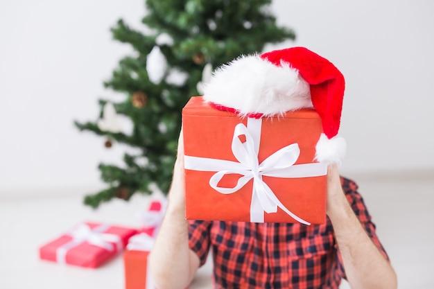 Weihnachts- und feiertagskonzept - lustiger mann mit weihnachtsmütze, der ein geschenk zu hause im wohnzimmer hält