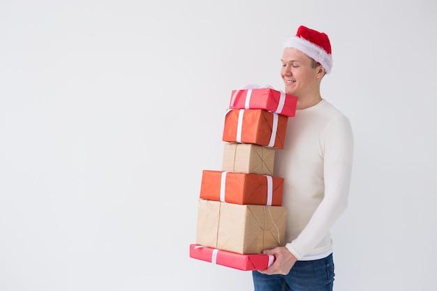 Weihnachts- und feiertagskonzeptmann in sankt-hut, der stapel geschenkboxen über weißem hintergrund hält