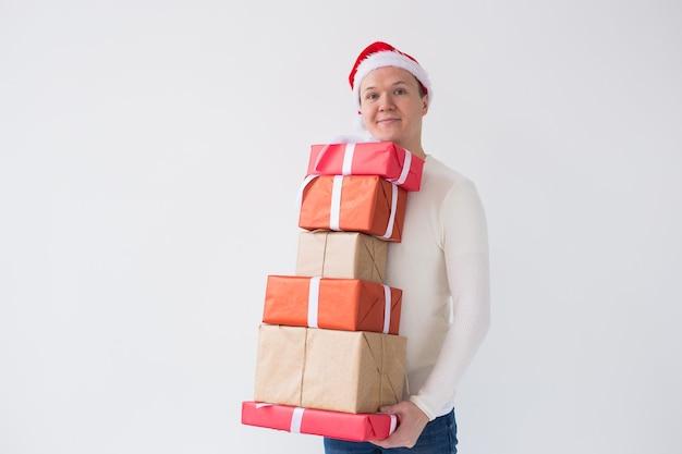 Weihnachts- und feiertagskonzeptmann in sankt-hut mit vielen geschenken auf weißem hintergrund mit kopienraum