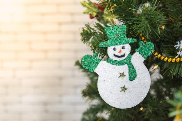 Weihnachts- und ferienzeit-konzept. abschluss der schneemannverzierung und -zubehörs auf weihnachtsbaum mit kopienraum.