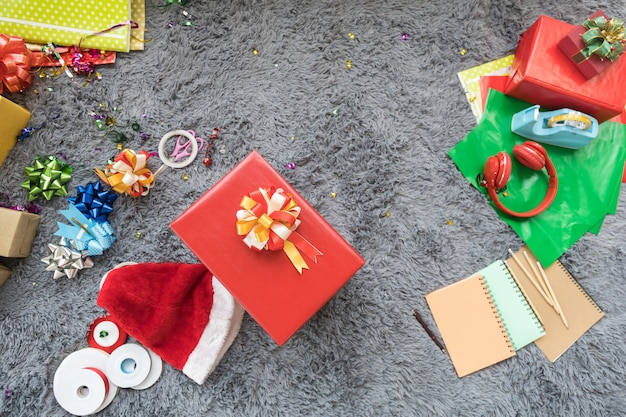 Weihnachts- und ferienzeit-konzept. schließen sie oben vom weihnachtshut und von der großen roten geschenkbox und verzieren sie zubehör, bleistift, notizbuch und kopfhörer auf grauem wollteppich im wohnzimmer.